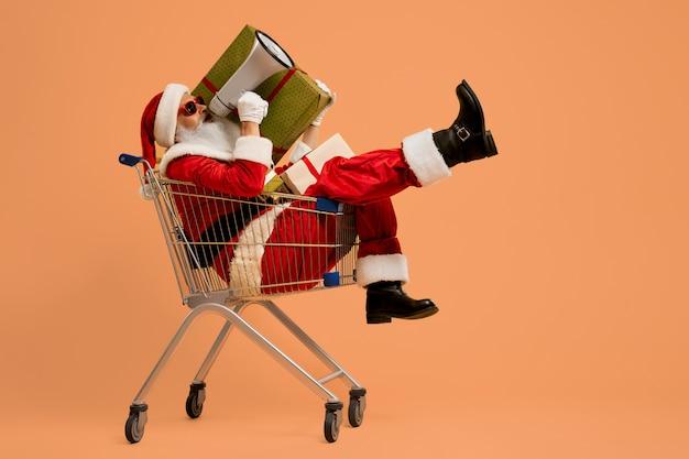 Santa gritando en megáfono mientras está sentado en el carrito de compras