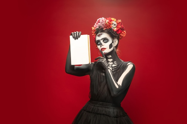 Santa muerte o calavera de azúcar con maquillaje brillante en rojo