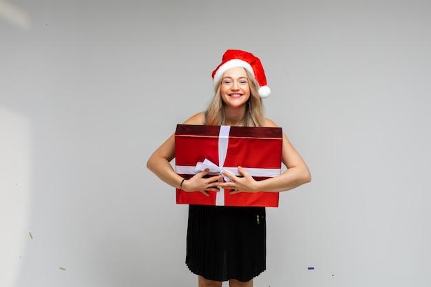 Santa niña con sombrero rojo con gran regalo festivo sonriendo posando sobre fondo gris con espacio de copia para el anuncio de año nuevo de navidad