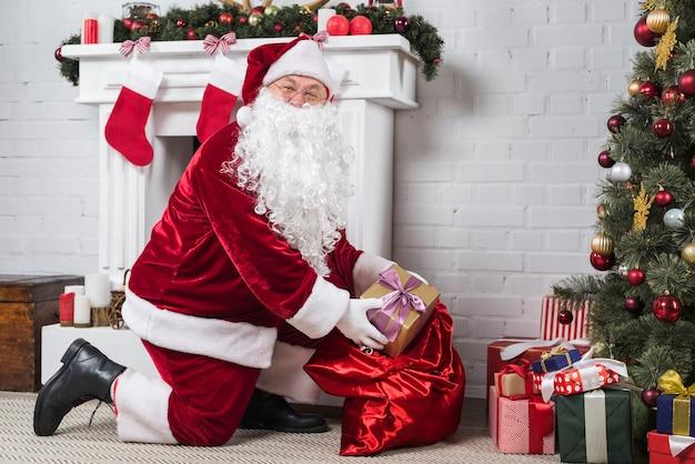 Santa poniendo regalos bajo el árbol de navidad decorado