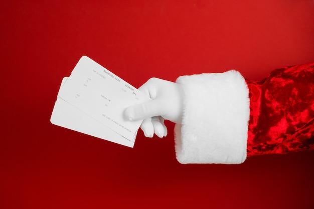 Santa sosteniendo boletos de embarque de avión en rojo
