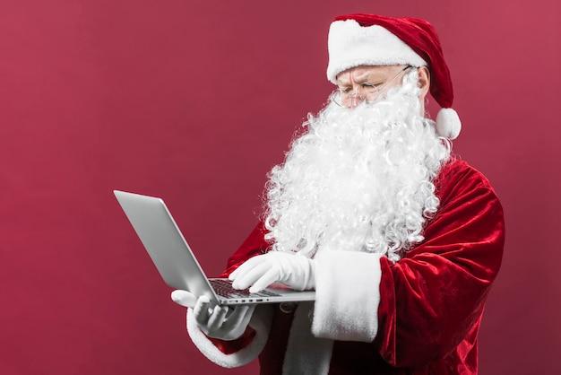 Santa en vasos escribiendo en la computadora portátil