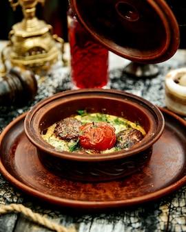Una sartén de cerámica con albóndigas de carne cocidas en huevo con espinacas cubiertas con tomate