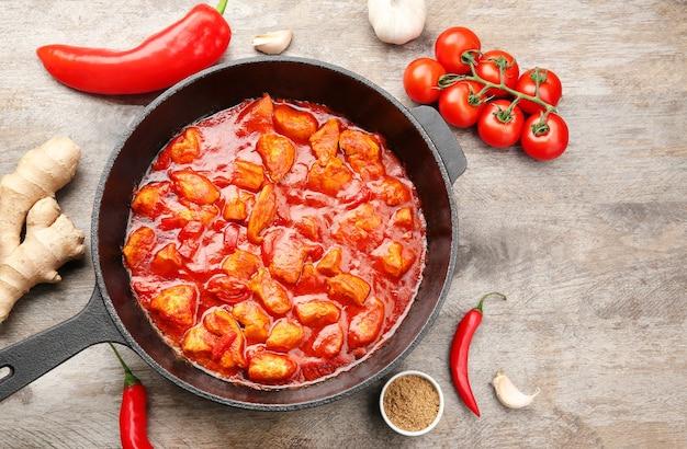 Sartén con delicioso pollo tikka masala en mesa de madera