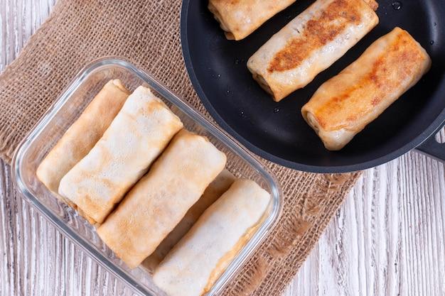 Sartén con panqueques, panqueques fritos en un recipiente de vidrio sobre mesa de madera. vista superior