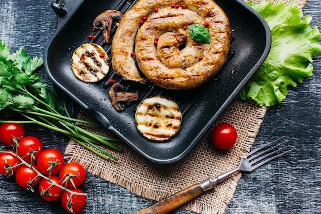 Sartén a la parrilla con deliciosas salchichas a la parrilla en espiral y vegetales.