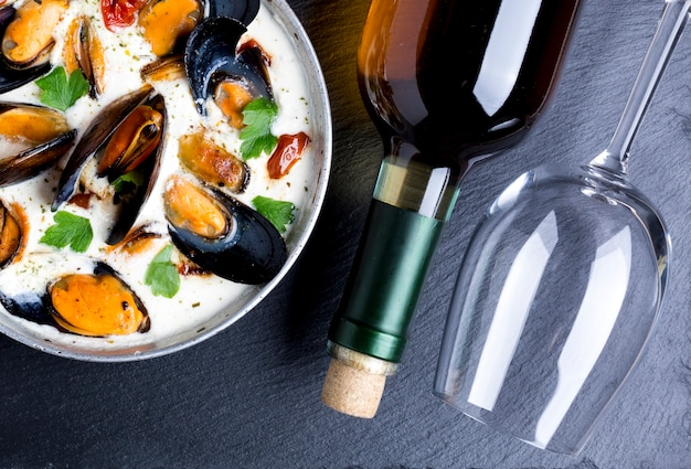 Sartén plana con mejillones en salsa blanca y botella de vino.
