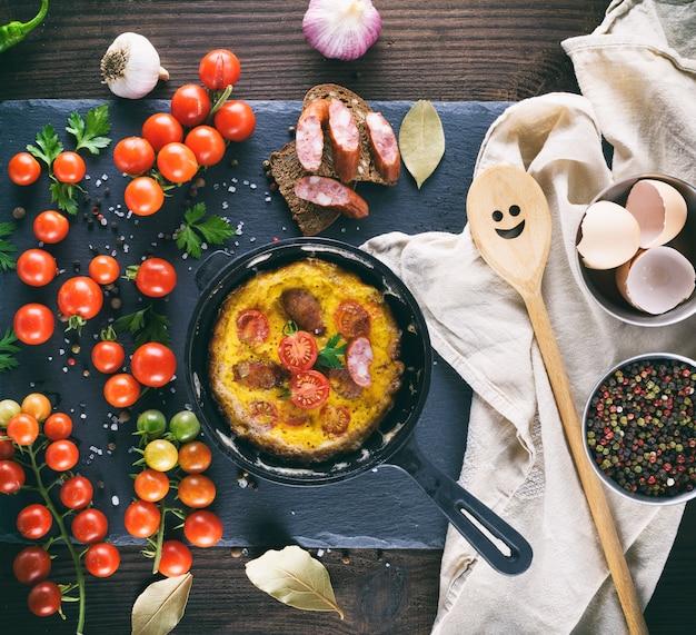 Sartén redonda con tortilla frita, huevos batidos con tomates cherry