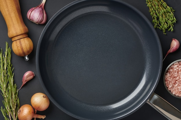 Sartén redonda vacía sobre fondo de mesa negro con especias y condimentos. utensilios de plancha para asar carne o verduras. vista superior con espacio para copiar texto.