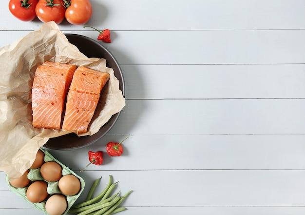 Sartén con salmón crudo, tomates y huevos sobre fondo de madera