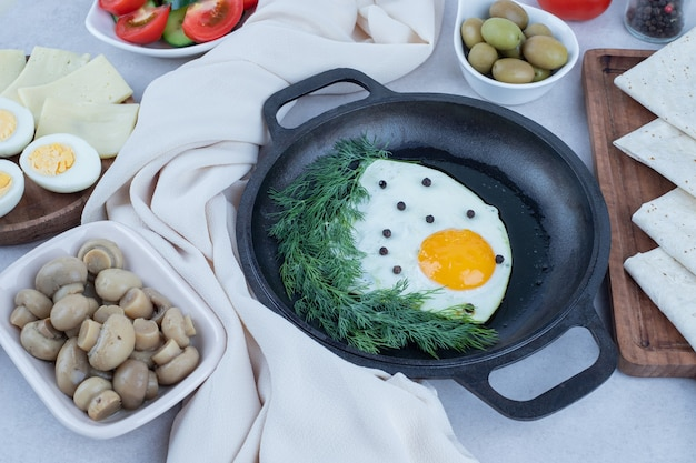Sartén con tortilla y huevos duros, queso, tomate, champiñones en blanco.