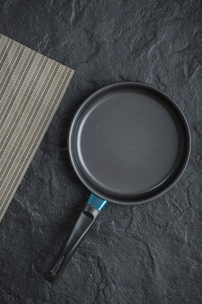 Sartén vacía para cocinar colocada sobre fondo negro