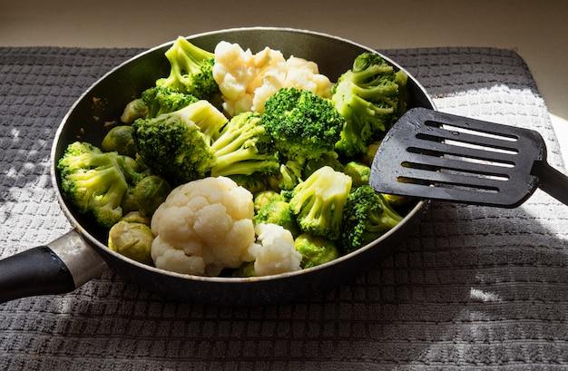 La sartén con verduras frescas descongeladas y espátula de cocina.