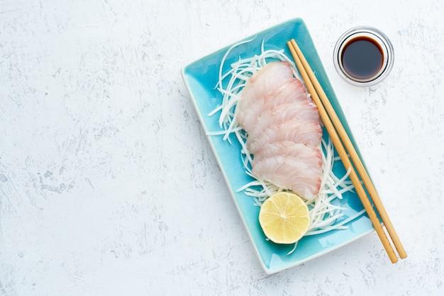 Sashimi de rodajas de filete de pescado blanco crudo en un plato azul sobre blanco