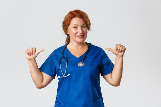 Sassy médico de mediana edad profesional, trabajadora médica en matorrales apuntando a sí misma y sonriendo, siendo hábil,