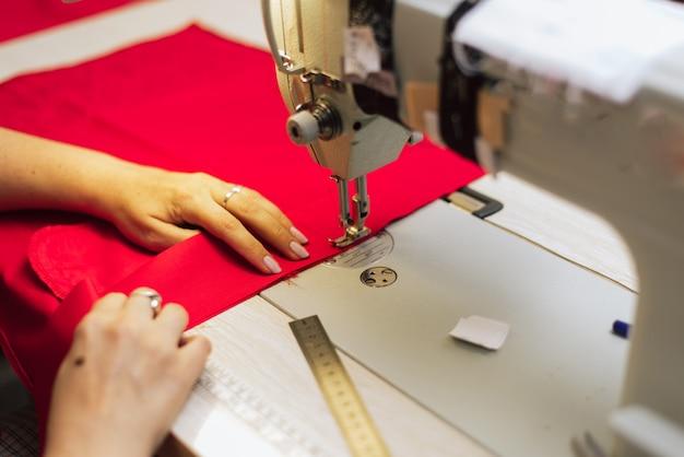 Un sastre borda con una máquina de coser sobre una tela tejida a ganchillo.