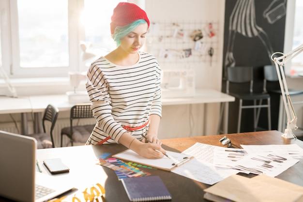 Sastre creativo femenino trabajando en el taller