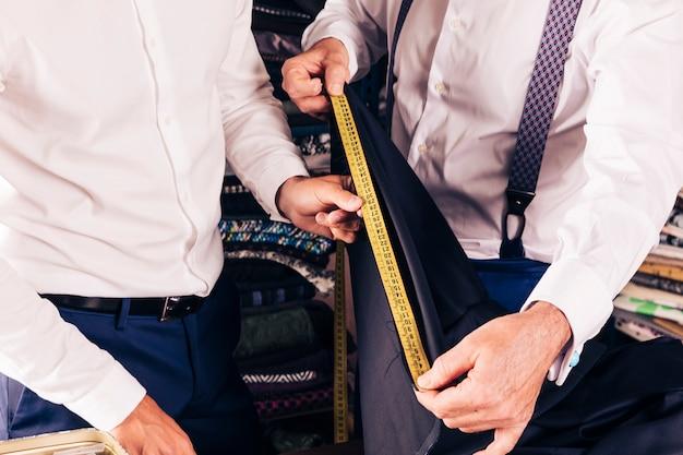 Sastre de hombre mayor y cliente midiendo la tela con mesa de medida amarilla.