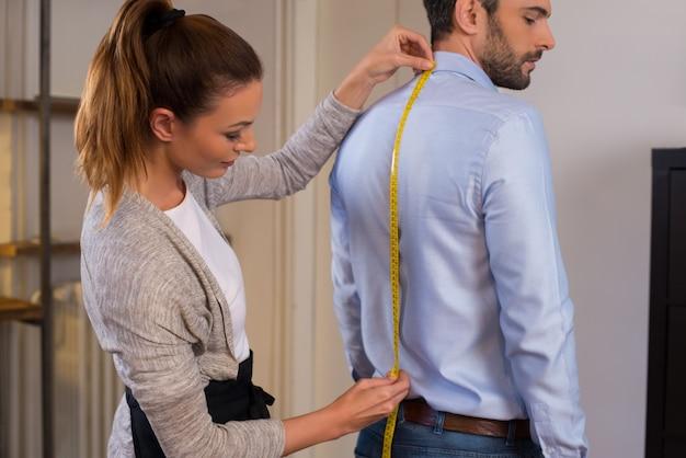 Sastre de pie cerca del cliente masculino midiendo hacia atrás. adaptar a la mujer tomando medidas para la nueva camisa de negocios con medidor de cinta. joven diseñador de moda tomando la medida del hombre vestido con camisa en la tienda.