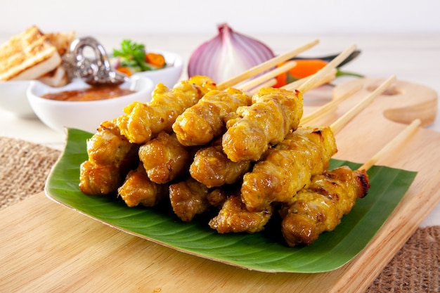 Satay de cerdo, cerdo a la parrilla servido con salsa de maní o salsa agridulce, comida tailandesa