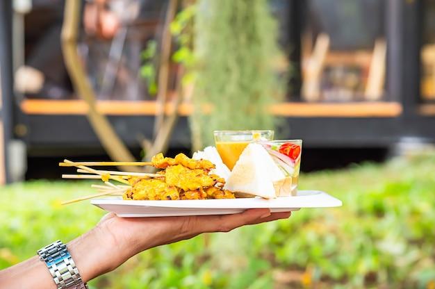 Satay de cerdo con leche de coco y pan con salsa de maní en plato de plástico blanco en la mano.