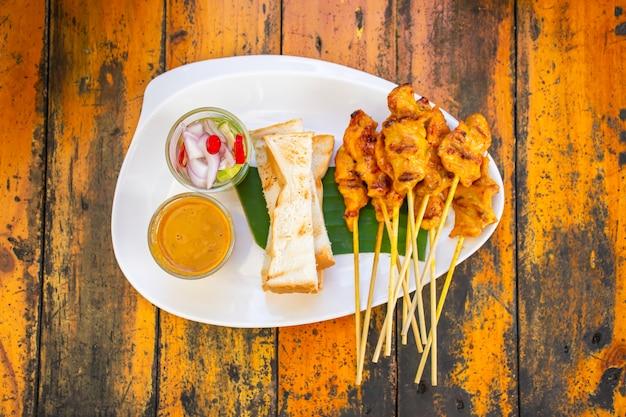 Satay de cerdo con leche de coco y pan con salsa en plato de plástico blanco sobre mesa de madera.