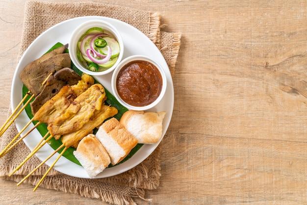 Satay de cerdo con su salsa de maní y encurtidos que son rodajas de pepino y cebolla en vinagre