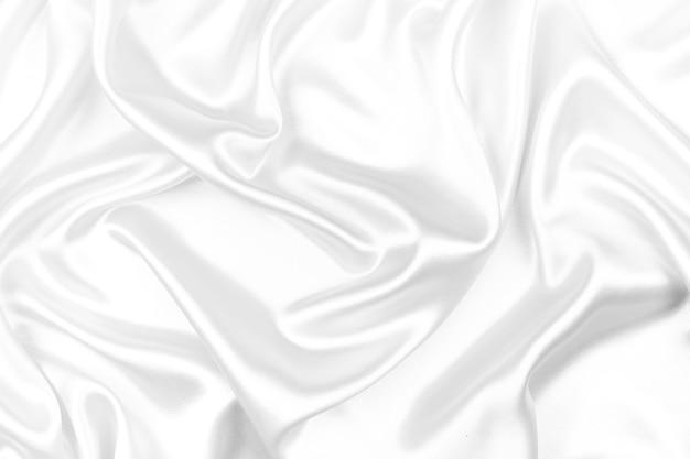 Satén lujoso de la textura de seda blanca para el fondo abstracto. enfoque suave