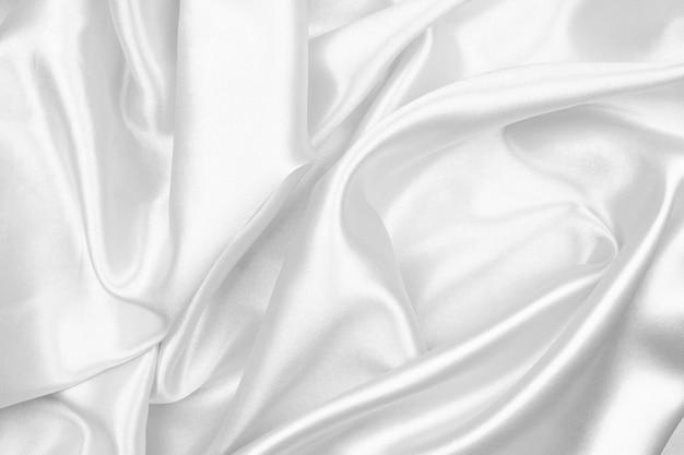 Satén lujoso de la textura de seda gris para el fondo abstracto