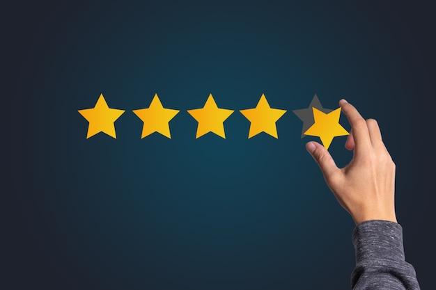 La satisfacción del cliente y el concepto de evaluación del servicio del producto, mano sosteniendo y poner la estrella amarilla a cinco estrellas con espacio de copia.
