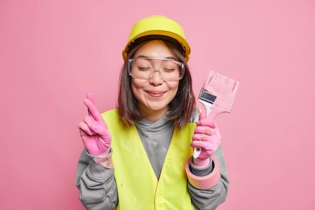 Satisfecha mujer asiática cruza los dedos sostiene pincel renueva casa hace deseo cree en buena suerte usa gafas de seguridad casco guantes