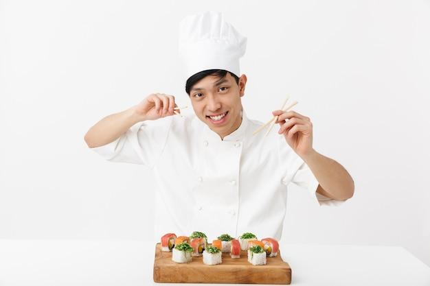 Satisfecho el hombre jefe chino en uniforme de cocinero blanco comiendo sushi con palillos aislados sobre la pared blanca