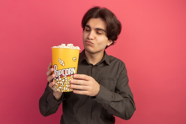 Satisfecho con los ojos cerrados chico guapo joven con camiseta negra sosteniendo un cubo de palomitas de maíz aislado en la pared rosa