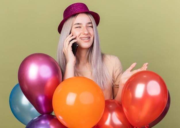 Satisfecho con los ojos cerrados joven hermosa que llevaba aparatos dentales con gorro de fiesta de pie detrás de globos habla por teléfono