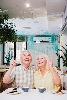 Satisfecho pareja de ancianos sentados en la cafetería