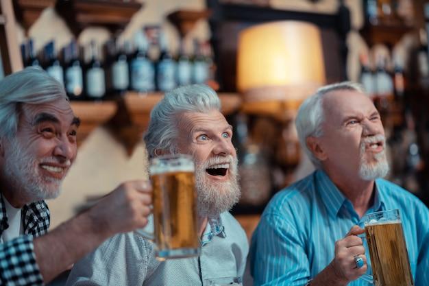 Satisfecho con el resultado. jubilados alegres que se sienten satisfechos con el resultado del partido de fútbol