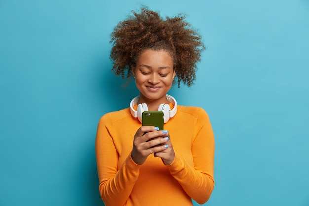 Satisfecho suscriptor afroamericano adicto a las redes sociales y las tecnologías modernas sostiene mensajes de texto de tipo celular usa auriculares estéreo alrededor del cuello vestida con ropa casual