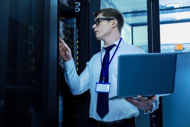 Satisfecho con el trabajo. hombre inteligente decidido trabajando con equipo y sosteniendo una computadora portátil