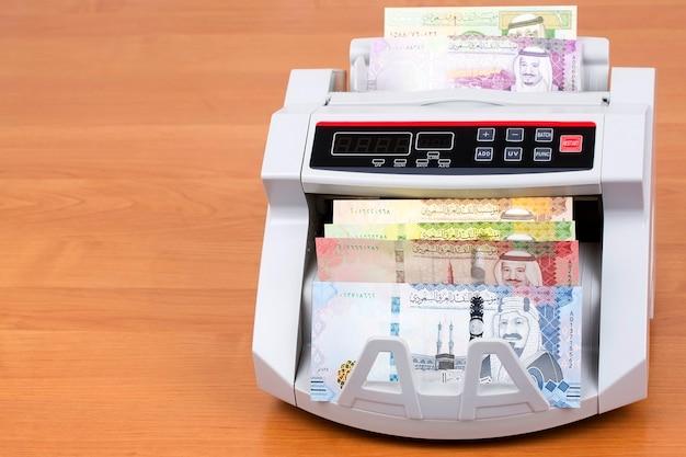 Saudi riyal en una máquina de contar