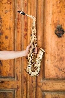 Saxofon dorado con fondo de madera.