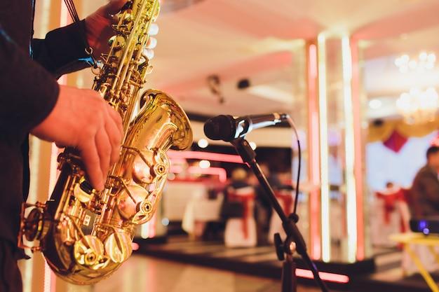 Saxofón dorado en manos de un músico cerca del micrófono.