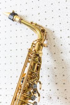 Saxofón de oro en el fondo de la pared blanca
