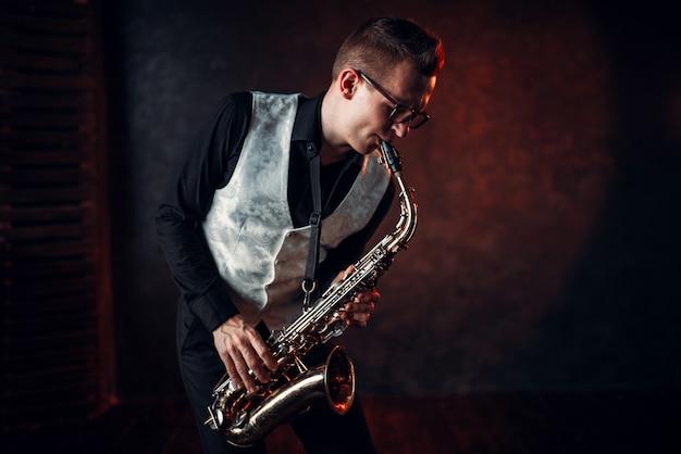 Saxofonista masculino profesional tocando melodía musical de jazz en el saxofón