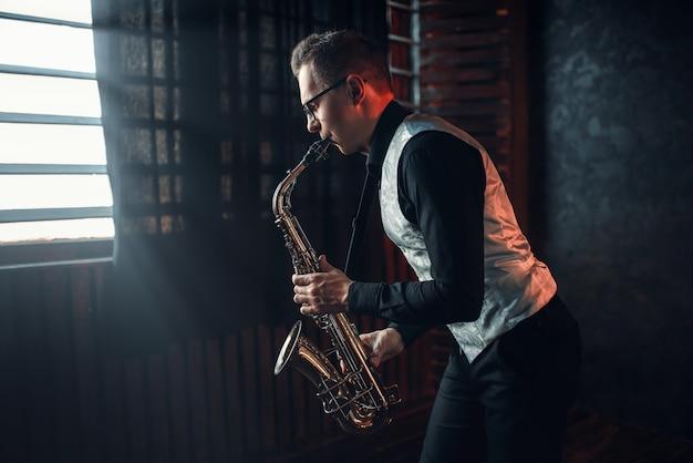 Saxofonista masculino tocando melodía de jazz en el saxofón contra la ventana