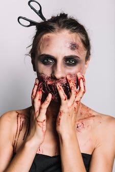 Scary mujer con tijeras en la cabeza tocando la cara