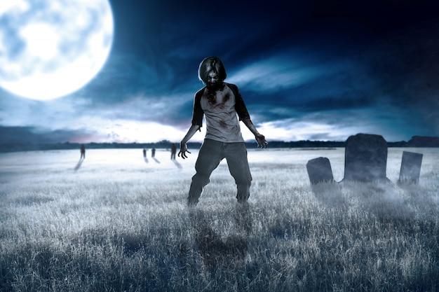 Scary zombies con sangre y heridas en su cuerpo caminando por el campo de hierba