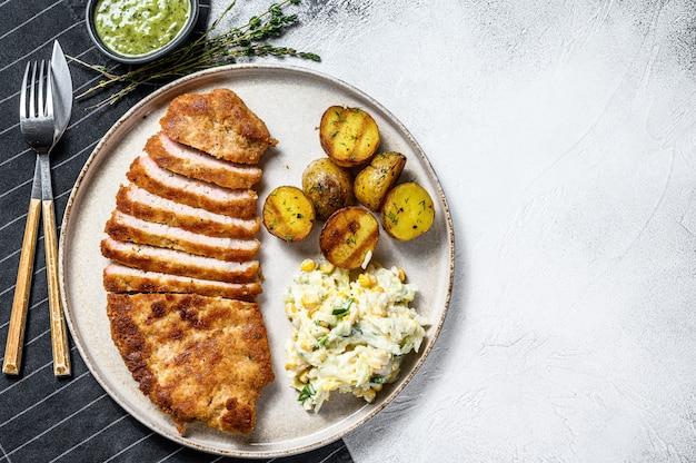 Schnitzel alemán weiner empanado casero con patatas y ensalada. fondo gris vista superior. copia espacio