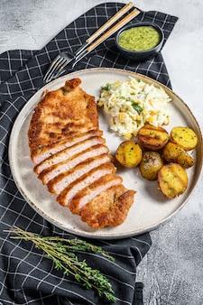 Schnitzel alemán weiner empanado casero con patatas y ensalada. fondo gris vista superior