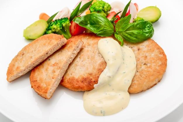 Schnitzel, chuleta de pollo con salsa blanca y verduras, sobre fondo blanco.