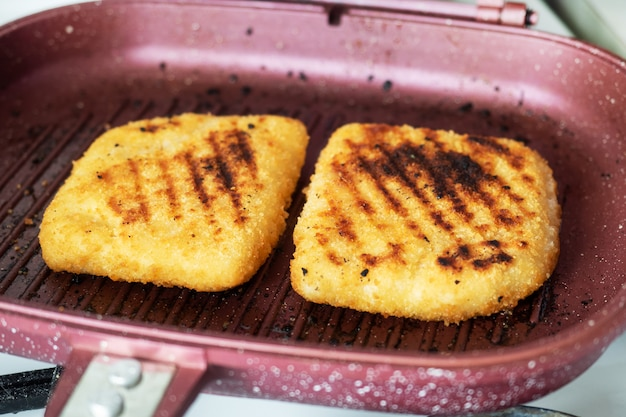 Schnitzel frito a la parrilla. dos piezas de cordon bleu con jamón y queso en una sartén.